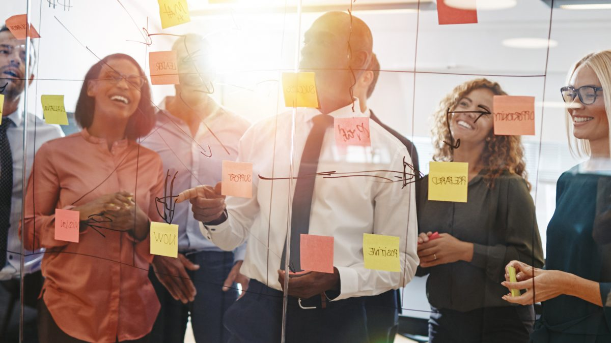 Young professionals brainstorming with sticky notes on a glass wall with his team while working together in a modern office